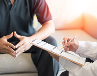 Urologist Doctor giving consult for prostate problems to patient. Urologic oncologists specialize in treating cancer of the urinary tract and male reproductive organs. Mens health problem concept.
